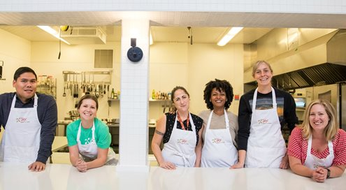 A group of people wearing aprons in a community kitchen